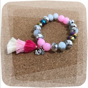Beaded bracelet with tassel and love charm.